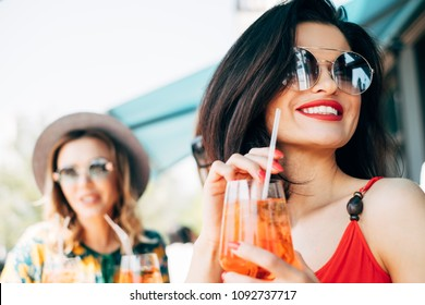Happy brunette woman with red lips holding iced aperol spritz