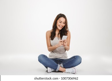 Happy brunette woman sitting on the floor and writing message on smartphone over gray background
