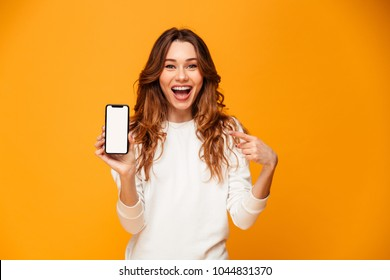 Happy brunette woman in sweater showing blank smartphone screen and pointing on it while looking at the camera over yellow background
