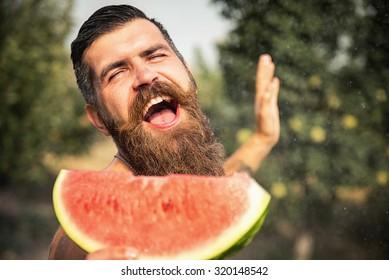 Happy brutal bearded man in the garden with juicy ripe watermelon