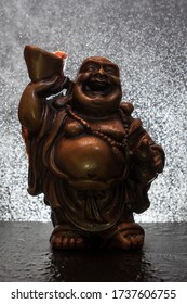 A happy buddha statue with water drops in the background forming a bokeh