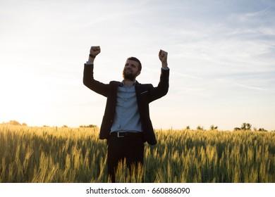 Happy buisinesman having fun in summer fields, man in buisines suit enjoy of freedom, concept of winner manager.