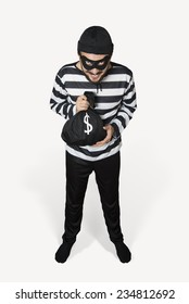 Happy Burglar on stand with his money bag, mask and hat.