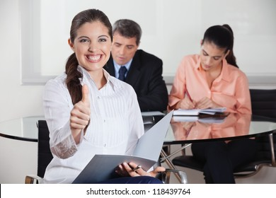 Happy busines woman with files in office holding her thumbs up
