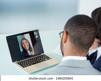Happy business colleagues chatting through video call. Office employees sitting at laptop, their young female colleague waving hello from screen. Video call concept