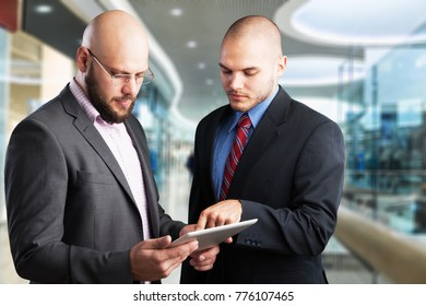 Happy business colleagues in modern office using digital tablet