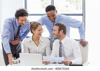 Happy business colleagues reviewing a report at desk in office