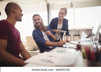 Happy business colleagues working together at creative office desk