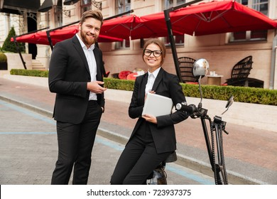 Happy business couple posing near the modern motorbike outdoors and looking at the camera