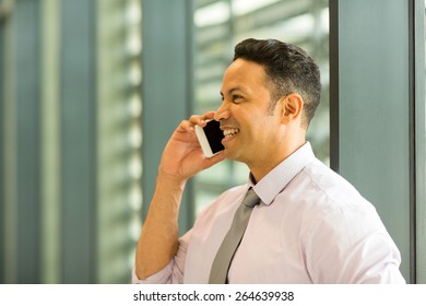 happy business executive talking on mobile phone in office