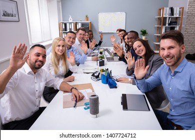 Happy Business Group Of Diverse People Waving Hands During A Meeting Conference In The Office