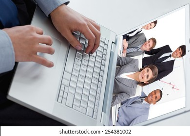 Happy business group having a meeting against angle view of hands typing