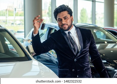 happy business indian man in well-dressed black suit buy new biodiesel eco automobile in lux showroom.