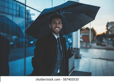 Happy business man with black jacket, gloves and umbrella Perletti under the rain. Filter Applied.