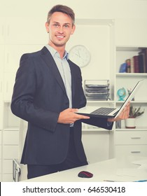 Happy business man in formalwear standing with laptop in hands in company office