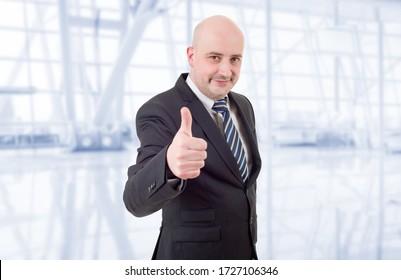 Heureux homme d'affaires qui monte le pouce, au bureau