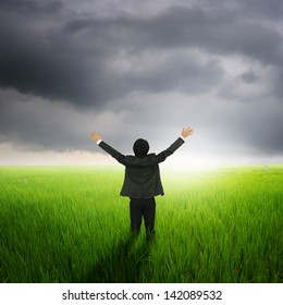 Happy business man  in green rice field and rainclouds