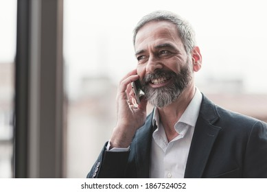 Happy business man having a talk on his phone, enjoying his work from home, standing beside the window