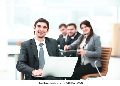 Happy business man holding a modern laptop computer with his team