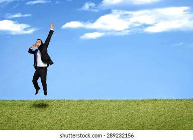 Happy business man jumping in landscape
