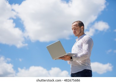 Happy business man looking to his laptop