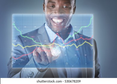 Happy business man looking at hologram showing financial graphs and stocks information analysing business information and data