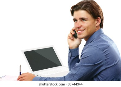 Happy business man on cell phone in front of laptop isolated on white background