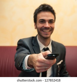 Happy business man pointing remote control. Selective focus image.