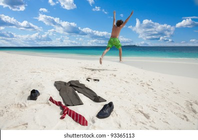 Happy business man running in to ocean to swim with clothes such as boots, tie and pants taken off and left on the white sand