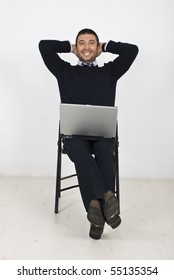 Happy  business man sitting on chair in a relaxed position with hands under head and holding a laptop