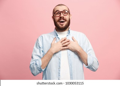Happy business man standing and smiling isolated on pink studio background. Beautiful male half-length portrait. Young emotional man. The human emotions, facial expression concept. Front view.