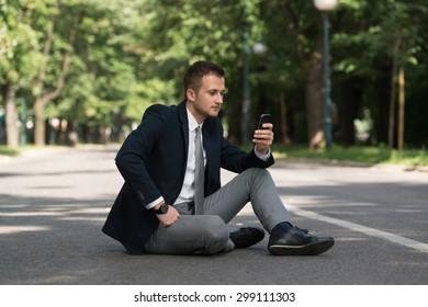 Happy Business Man Using Mobile Phone Outside Sitting On Asphalt