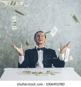 Happy business man very rich guy throw money dollar bills in air like rain money bill and banknotes US dollar bill on the table - business success concept