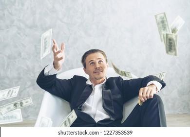 Happy business man very rich guy throw money dollar bills in air like rain money bill and banknotes US dollar bill on the bathtub - business success concept