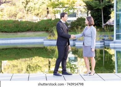 Happy Business Man and Woman Shaking Hands in Park