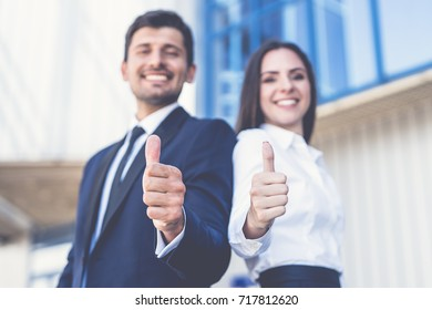 The happy business man and woman thumb up