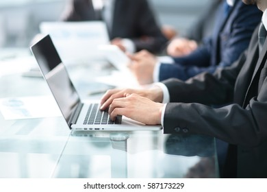 Happy business man working a modern laptop computer with his team in background