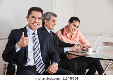 Happy business manager holding his thumbs up with team in the background