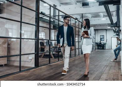 Happy business partners. Full length of two young colleagues in smart casual wear discussing business and smiling while walking through the office corridor