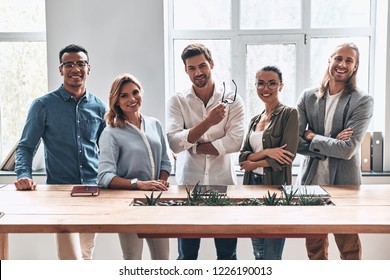 Happy business partners. Group of young modern people in smart casual wear looking at camera and smiling while standing in the creative office