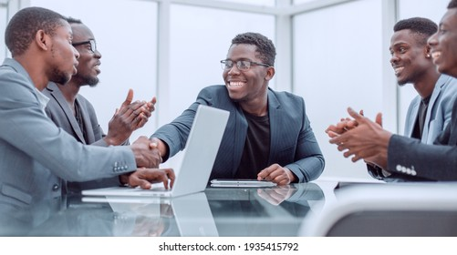 happy business partners shaking hands at meeting in the office.