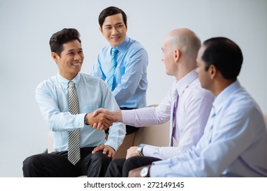 Happy business partners shaking hands after successful deal