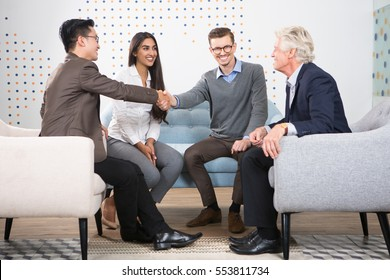 Happy Business Partners Shaking Hands at Meeting