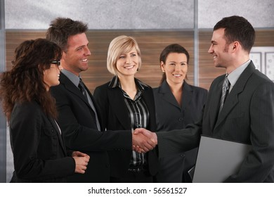 Happy business partners shaking hands in meeting room, smiling.