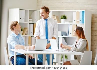 Happy business partners talking at break between working hours