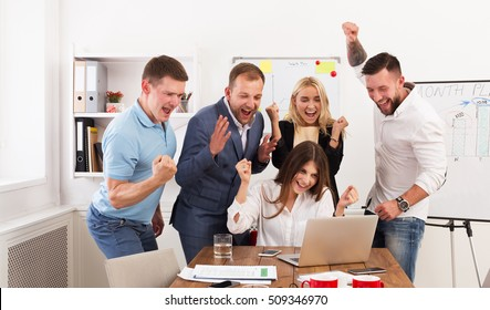 Happy business people celebrate success looking at laptop screen in the office. Successful corporate team of partners and coworkers