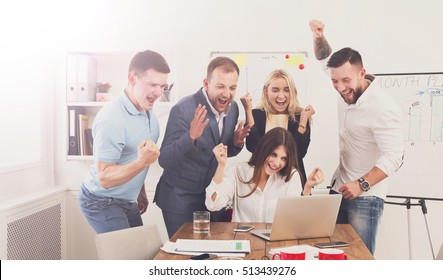 Happy business people celebrate success looking at laptop screen in the office. Successful corporate team of partners and coworkers, winners excited of victory