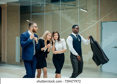 Happy business people celebrate success in the office. Successful corporate team of partners and coworkers, winners excited of victory