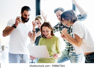 Happy business people celebrate the successful project realization while looking at laptop screen in the office. Successful corporate team of partners and coworkers are  excited with the victory.