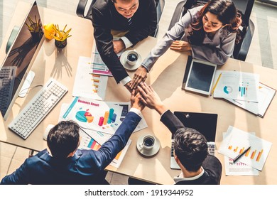 Happy business people celebrate teamwork success together with joy at office table shot from top view . Young businessman and businesswoman workers express cheerful victory showing unity and support .